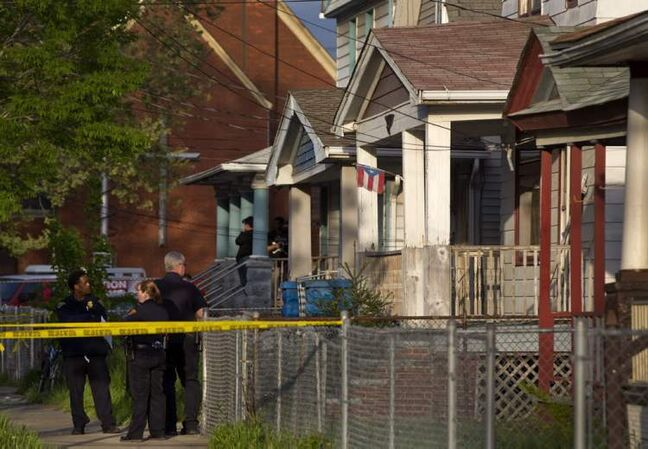 Cleveland Police stand outside a home where they say missing women Amanda Berry, Gina DeJesus and Michele Knight were found in the 2200 block of Seymour Avenue in Cleveland on Monday, May 6, 2013.