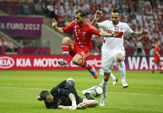 Russia's Alexander Kerzhakov jumps over Poland goalkeeper Wojciech Szczesny during the Euro 2012 soccer championship Group A match between Poland and Russia in Warsaw, Poland, Tuesday, June 12, 2012. On the right is Poland's Marcin Wasilewski.
