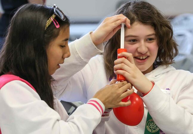 Prairie Rose School students Shaylynne Grove, Grade 6, left, helps Kristen Jolly, Grade 5, pump up a balloon for a science experiment at the 44th Annual Winnipeg Schools' Science Fair on Wednesday.