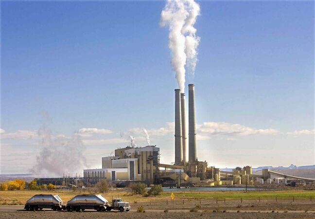 This Oct. 23, 2009, file photo shows coal trucks leaving the coal-fired Hunter Power Plant just south of Castle Dale, Utah after making a delivery.