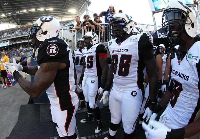 Former Winnipeg Blue Bombers player Jovon Johnson, left, now playing with the Ottawa Redblacks, leads his team onto the field for the Redblacks' first-ever CFL game at Investors Group Field in Winnipeg.