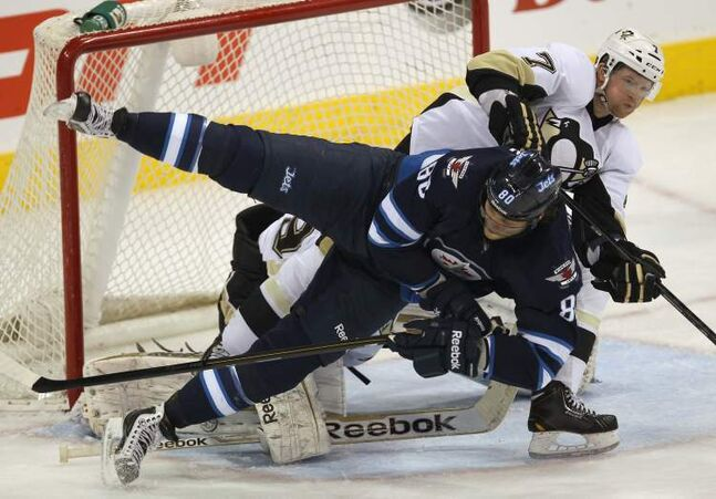 Pittsburgh Penguins Paul Martin upends Winnipeg Jets Nik Antropov in front of the net during second period NHL action against the Winnipeg Jets Friday night in Winnipeg.