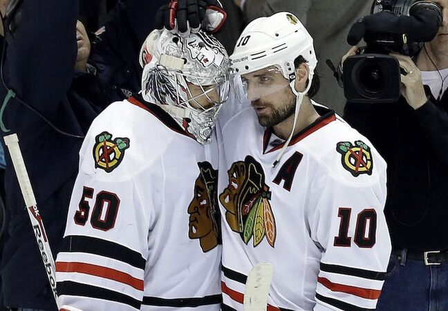 Chicago Blackhawks goalie Corey Crawford is congratulated by Chicago Blackhawks center Patrick Sharp after the 4-3 victory.