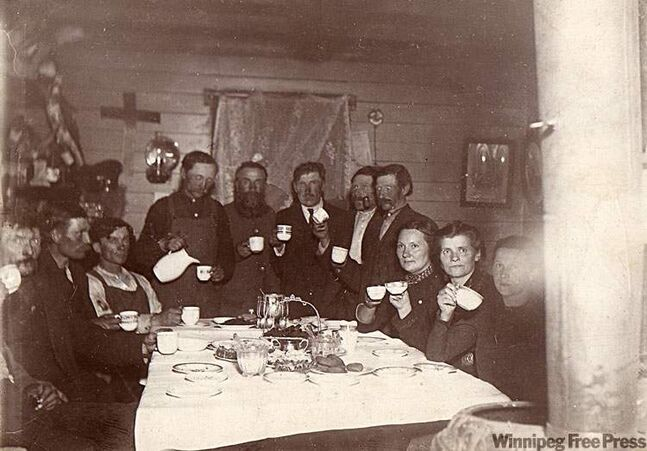 Immigrants from Iceland crowd into a room to pose drinking coffee.