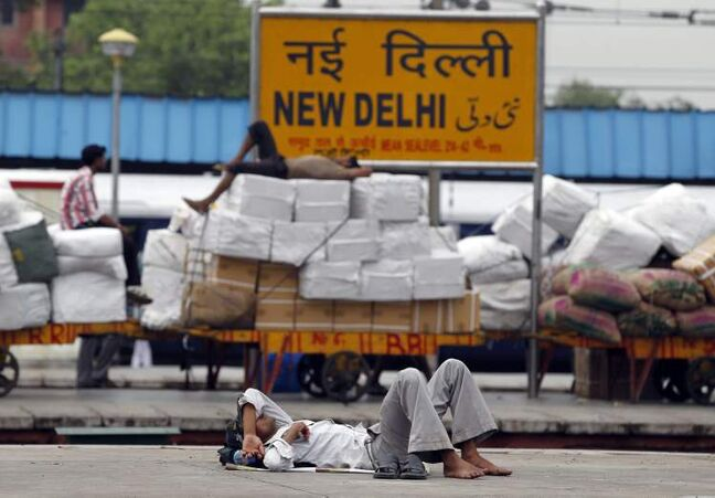 Indian laborers sleep on railway platforms at the New Delhi railway station following a power outage in New Delhi, India, Tuesday, July 31, 2012. India's energy crisis cascaded over half the country Tuesday when three of its regional grids collapsed, leaving more than 600 million people without government-supplied electricity. (AP Photo/Mustafa Quraishi)