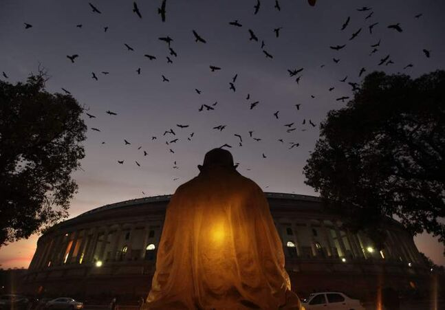 Mahatma Gandhi's statue overlooks Indian parliament house as Indian lawmakers debate on Foreign Direct Investment (FDI) , in New Delhi, India, Wednesday, Dec. 5, 2012. India's ruling Congress Party-led coalition government on Wednesday won a crucial vote in favor of its decision to open up the country's huge retail sector to foreign big-box companies like Wal-Mart, a move that its opponents said will crush small shop owners and farmers. (AP Photo/Manish Swarup)