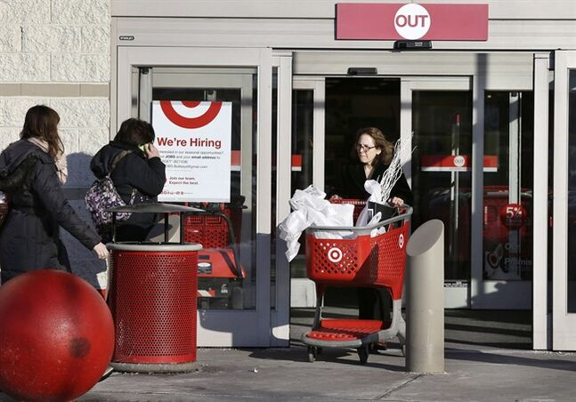 A woman pushes a shopping cart departing a Target retail store Dec. 19, 2013 in Watertown, Mass. THE CANADIAN PRESS/AP, Steven Senne