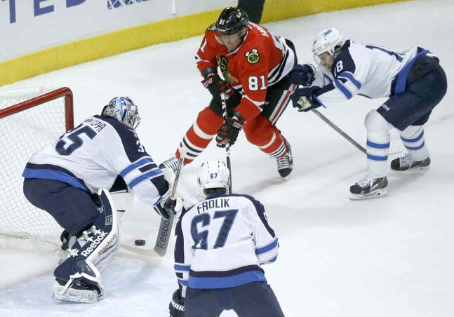 Jets goalie Al Montoya stymies Blackhawks forward Marian Hossa.