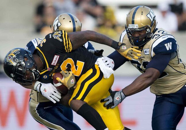 Hamilton Tiger-Cats' running back C.J. Gable, left, gets tackled by Winnipeg Blue Bombers' defensive tackle Bryant Turner, right, during first half of Thursday's game.