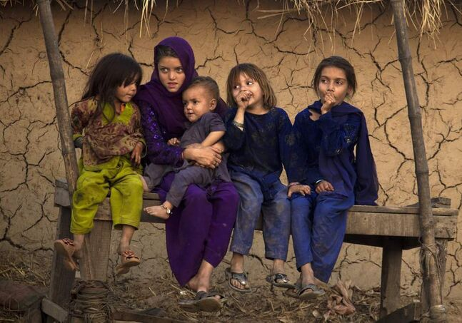Pakistani children who are displaced from their villages in Bajur due to fighting between militants and security forces, sit along a roadside in Islamabad, Pakistan on Friday, Nov. 2, 2012. (AP Photo/B.K. Bangash)