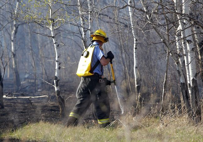 A fire crew member sprays the ground.