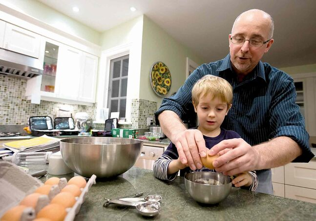Samuel Collins, 4, demonstrates how he makes pancakes with a little help from his father, David Collins.