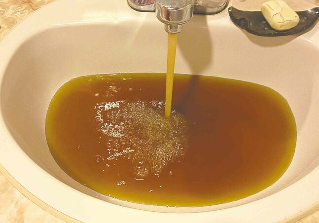 Brown water fills a bathroom sink in a North End home last September.