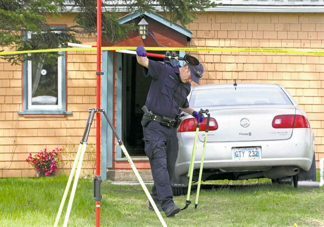 RCMP officers work at the scene of a suspicious death in MacGregor Monday.