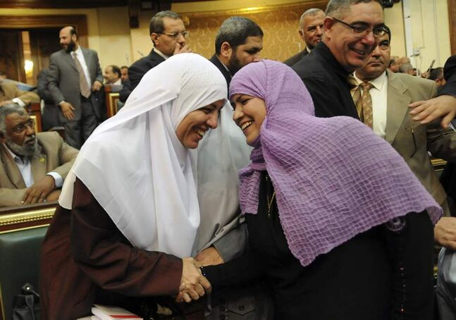 Two female Egyptian lawmakers greet each other at a brief session of Parliament, the first since the country's high court ruled the chamber unconstitutional, in Cairo, Egypt. Egypt's Islamist-dominated parliament convened Tuesday in defiance of a ruling by the country's highest court and swiftly voted to seek a legal opinion on the decision that invalidated the chamber over apparent election irregularities. (AP Photo/Mohammed Asad)