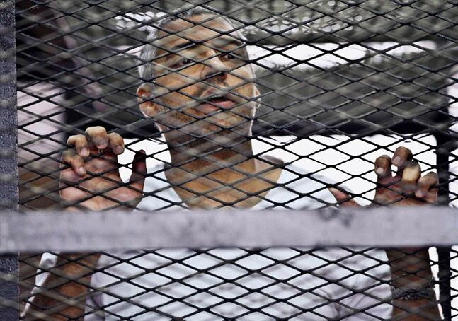 Mohammed Fahmy, Canadian-Egyptian acting bureau chief of Al-Jazeera, appears in a defendant's cage at a courtroom in Cairo, Egypt, May 5, 2014. The family of Fahmy, convicted on terrorism-related charges by a Cairo court, says the 40-year-old is in a
