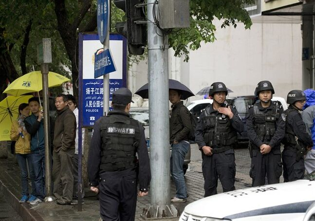 People watch armed policemen standing guard near the site of an explosion in Urumqi, northwest China's Xinjiang region, Thursday, May 22, 2014. Assailants in two SUVs plowed through shoppers while setting off explosives on a busy street market in China's volatile northwestern region of Xinjiang on Thursday, the local officials said, killing over two dozen people and injuring more than 90. The attack was the bloodiest in a series of violent incidents that Chinese authorities have blamed on radical separatists from the country's Muslim Uighur minority. (AP Photo/Andy Wong)