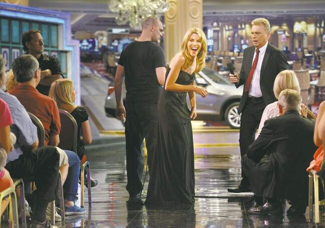 Vanna White, centre, who has been turning letters on Wheel of  Fortune for 30 years, laughs while interacting with the audience with host Pat Sajak (right) during a July taping in Las Vegas.