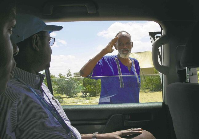 Ahmed Warsame is well-liked and and respected by both refugees and members of the local community. A refugee salutes him while he drives around Dadaab.