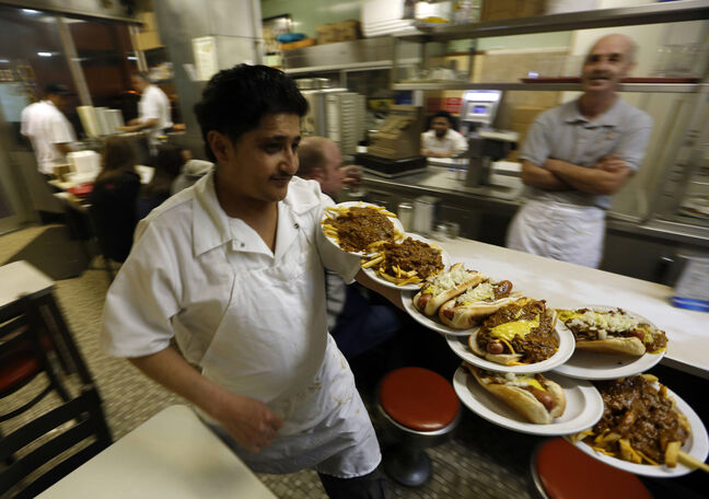 Faisal Ali delivers orders at Lafayette Coney Island in Detroit last month. The dog remains a gastric constant in a city that's seen its people, businesses and, at times, its hope flee.