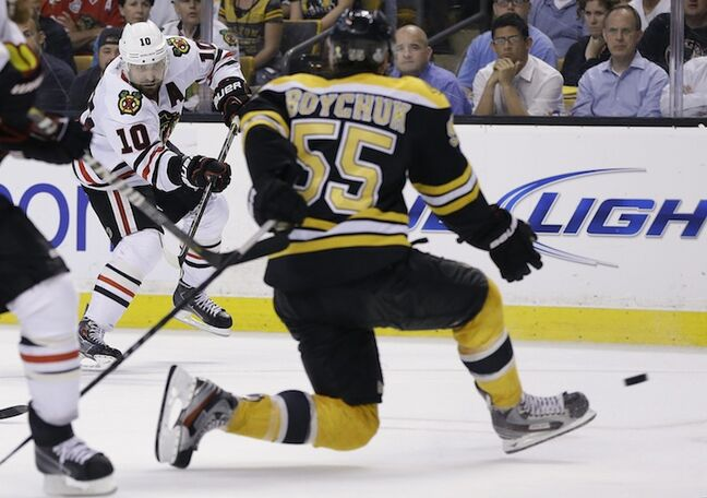 Chicago Blackhawks center Patrick Sharp shoots, and Boston Bruins defenceman Johnny Boychuk blocks the puck in the third period.
