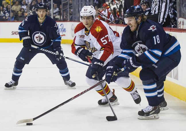 Winnipeg Jets  Bryan Little (#18) reaches for the puck against Florida Panthers Michael Goc (#57) as Winnipeg Jets Tobias Enstrom (#39) looks on during the second period.