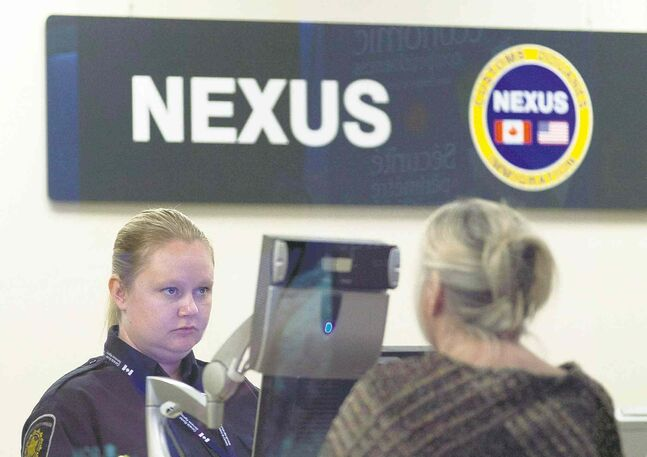A Canada Border Services Agency officer speaks with a traveller at the Nexus office at the airport in Ottawa.