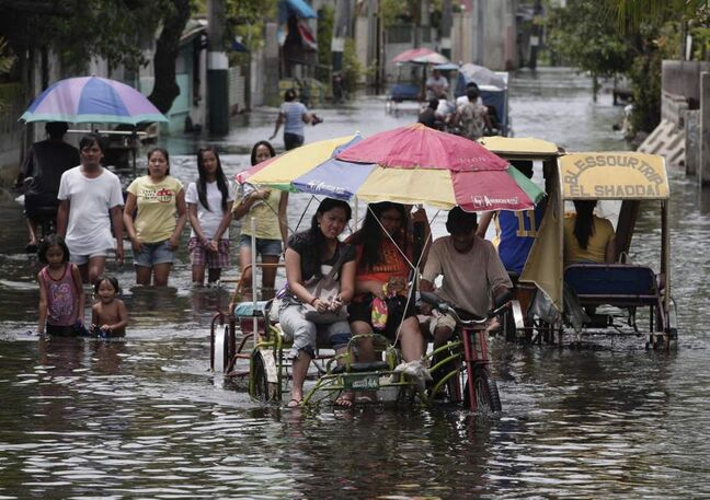 Residents negotiate a flooded street at Obando town, north of Manila. Typhoon Saola dumped torrents of rain as it swept past the Philippines, killing at least seven people and displacing more than 20,000 others by Tuesday. (AP Photo/Aaron Favila)