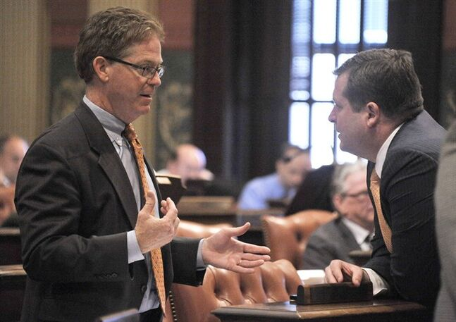 Rep. John Walsh, R-Livonia, left, talks over the votes on Detroit bailout bills with Speaker of the House, Jase Bolger, R-Marshall, Thursday, May 22, 2014 on the floor of the Michigan House of Representatives in Lansing, Mich. The Michigan House has approved Detroit bankruptcy legislation that commits $195 million in state money to prevent deeper cuts in retiree pensions and the sale of city-owned art. The House voted 74-36 Thursday to spend money to match contributions from foundations and the Detroit Institute of Arts. Eleven bankruptcy-related bills cleared the Republican-led chamber and go to the Senate. (AP Photo/Detroit News, Dale G. Young) DETROIT FREE PRESS OUT; HUFFINGTON POST OUT