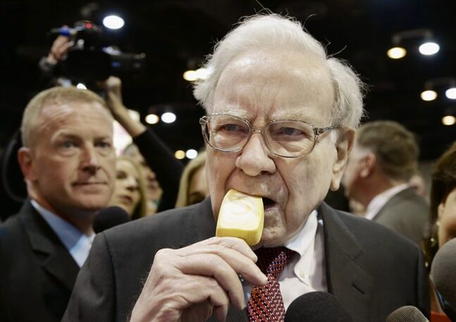 Berkshire Hathaway Chairman and CEO Warren Buffett eats an ice cream bar while touring the exhibition floor prior to the annual shareholders meeting on Saturday, May 3, 2014, in Omaha, Neb. More than 30,000 shareholders are expected to fill the CenturyLink Arena to hear Buffett and Berkshire Vice Chairman Charlie Munger discuss their business. (AP Photo/Nati Harnik)