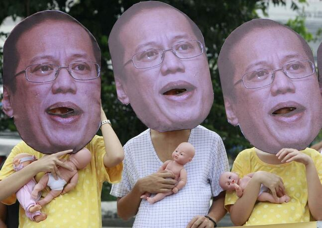 Wearing masks of Philippine President Benigno Aquino III, protesters calling for Aquino to prioritize and pass the reproductive health bill hold baby dolls during a rally to coincide with the president's third State of the Nation address at suburban Quezon city, northeast of Manila, Philippines. In their statement, protesters claim the quick passage of the bill can curb the rising deaths of Filipino mothers upon hearing the 2011 Family Health Survey by the Department of Health that reports 12 Filipino women die every day due to maternal complications. (AP Photo/Bullit Marquez)