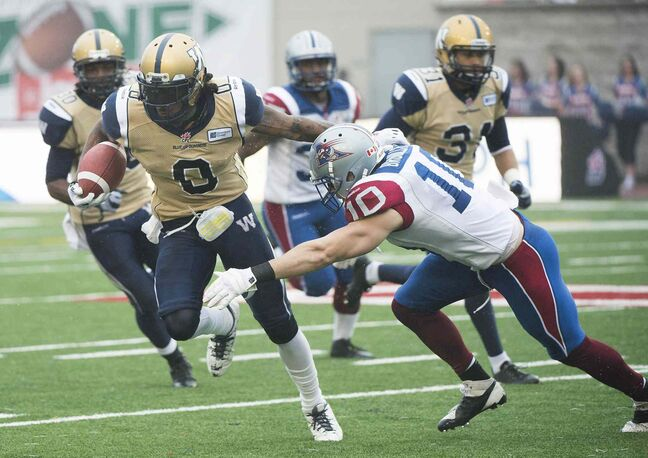 Winnipeg Blue Bombers' Johnny Sears, left, is tackled by Montreal Alouettes' Marc-Olivier Brouillette during first half CFL football action in Montreal Monday.
