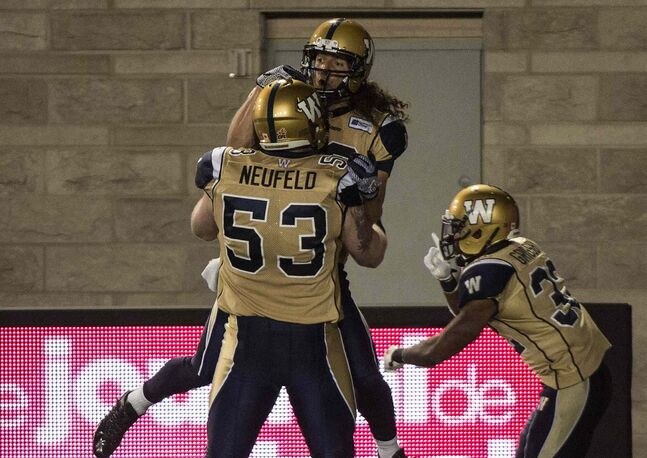 Winnipeg Blue Bombers' wide receiver Julian Feoli-Gudino leaps into the arms of teammate Patrick Neufeld after scoring a touchdown against the Montreal Alouettes in the final minutes of the fourth quarter Friday. The Blue Bombers beat the Alouettes 34-33.