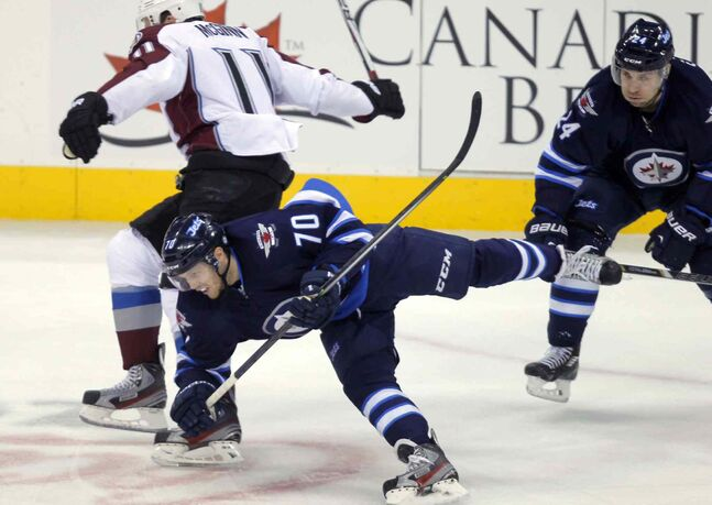 Winnipeg Jets John Albert (front) falls to the ice after being checked by Jamie McGinn (left) as Jets defenceman Grant Clitsome skates by.