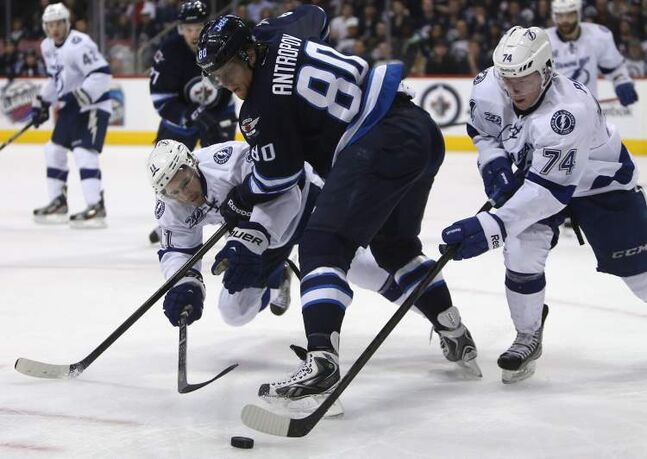 Winnipeg Jets' Nik Antropov battles for the puck between Tampa Bay Lightnings' Tom Pyatt (left) and Ondrej Palat during the second period pf an NHL game in Winnipeg, Sunday.