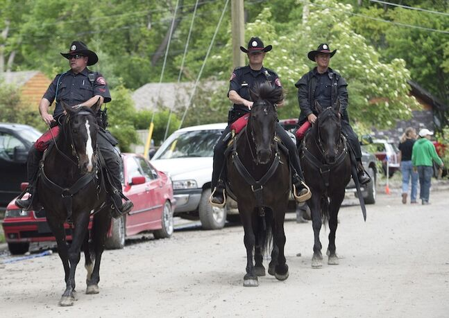 City of Calgary Police officers patrol the community of Bowness in Calgary on horseback Monday.