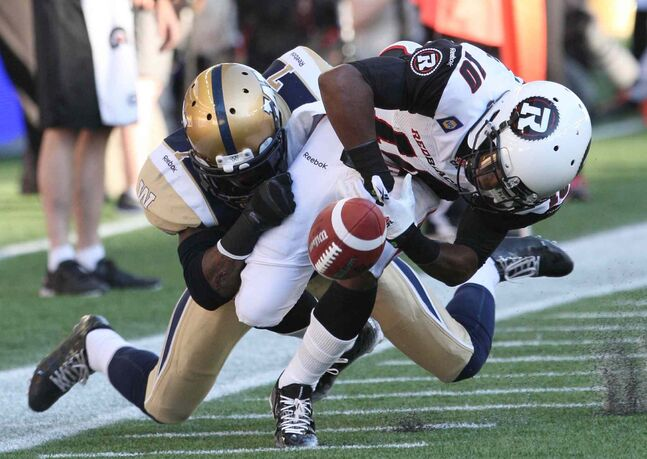 Winnipeg Blue Bombers' Demond Washington strips the ball from  Ottawa Redblacks' Kierre Johnson during the first half of Thursday's game.