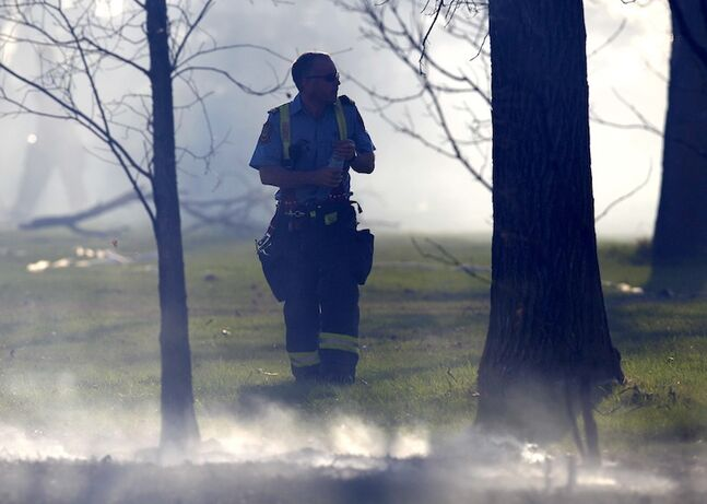 A fire crew member walks between areas of smoldering grass.