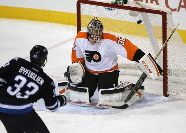 Winnipeg Jets Dustin Byfuglien shoots one by Philadelphia Flyers goaltender Steve Mason during the first period.
