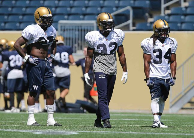 From left, Winnipeg Blue Bombers running back hopefuls Kevin Smith, Nic Grigsby and Paris Cotton strut their stuff at Investors Group Field on Thursday.