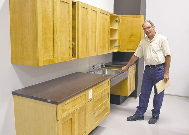 Larry Daniuk, of The Timeless John, with a set of solid-maple cabinets designed to accommodate wheelchair-bound individuals.