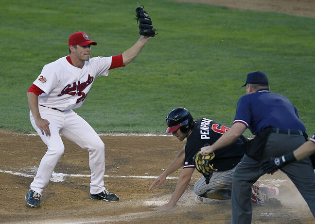 Pitcher Matt Rusch (29) gets Redhawks' Zach Penprase out at home.