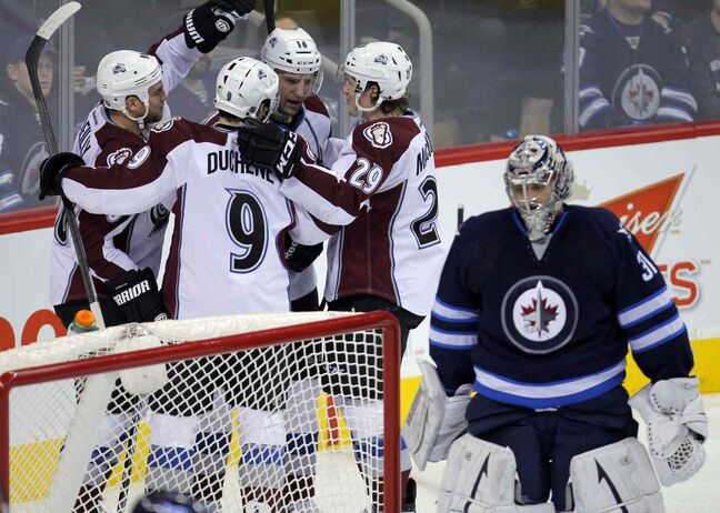 Members of the Colorado Avalanche celebrate a goal in the second period behind Jets goaltender Ondrej Pavelec.013
