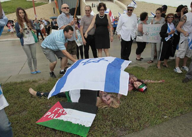 An Israel supporter places a flag over Palestinian supporters who were taking part in a 'die-in'as about 100 people gather for a pro-Israel rally in downtown Winnipeg Monday.