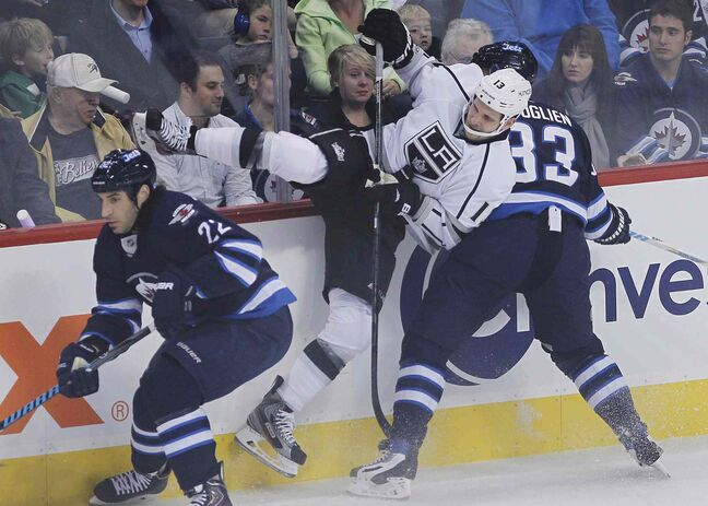 Winnipeg Jets' Dustin Byfuglien (33) takes out Los Angeles Kings' Kyle Clifford (13) as Jets' Chris Thorburn (22) chases down the puck during the first period.