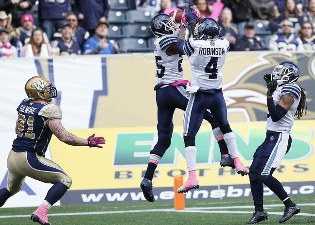 Toronto Argonauts' Patrick Watkins (25) and Jamie Robinson (4) knock down the touchdown pass intended for Winnipeg Blue Bombers' JT Gilmore (91) during the first half.