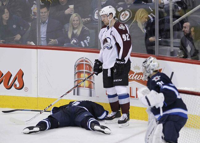 Colorado Avalanche skater Gabriel Landeskog (centre) stands over Winnipeg Jets defenceman Mark Stuart (left) after checking him head-first into the boards as Jets goaltender Ondrej Pavelec looks on in the third period.