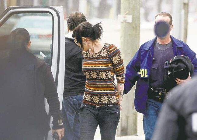 Officers, their faces obscured to protect their identity, take a woman into custody at the location. Wednesday's head-shop raids were conducted by city police and the RCMP.