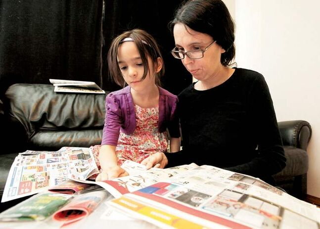 Nadine  Chappellaz  and her daughter Lea, 7, look through flyers  for deals.