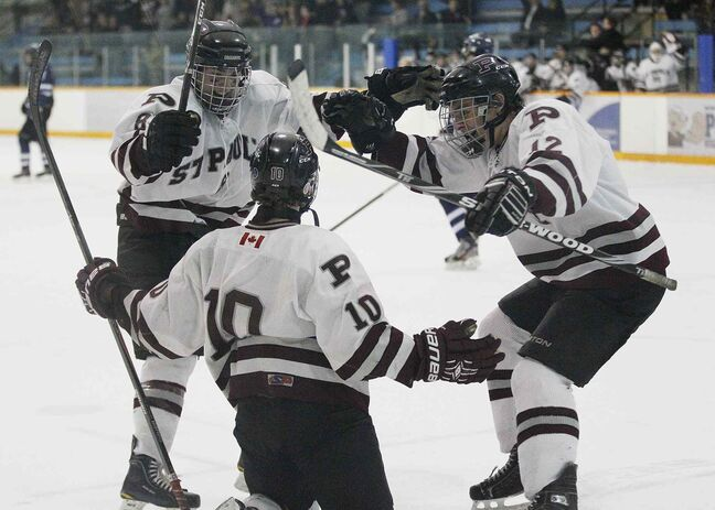 The St. Paul's Crusaders Cole Zadro (10), Alex Bouchard (left) and Xander Tachinski celebrate Zadro's goal against the River East Kodiaks.